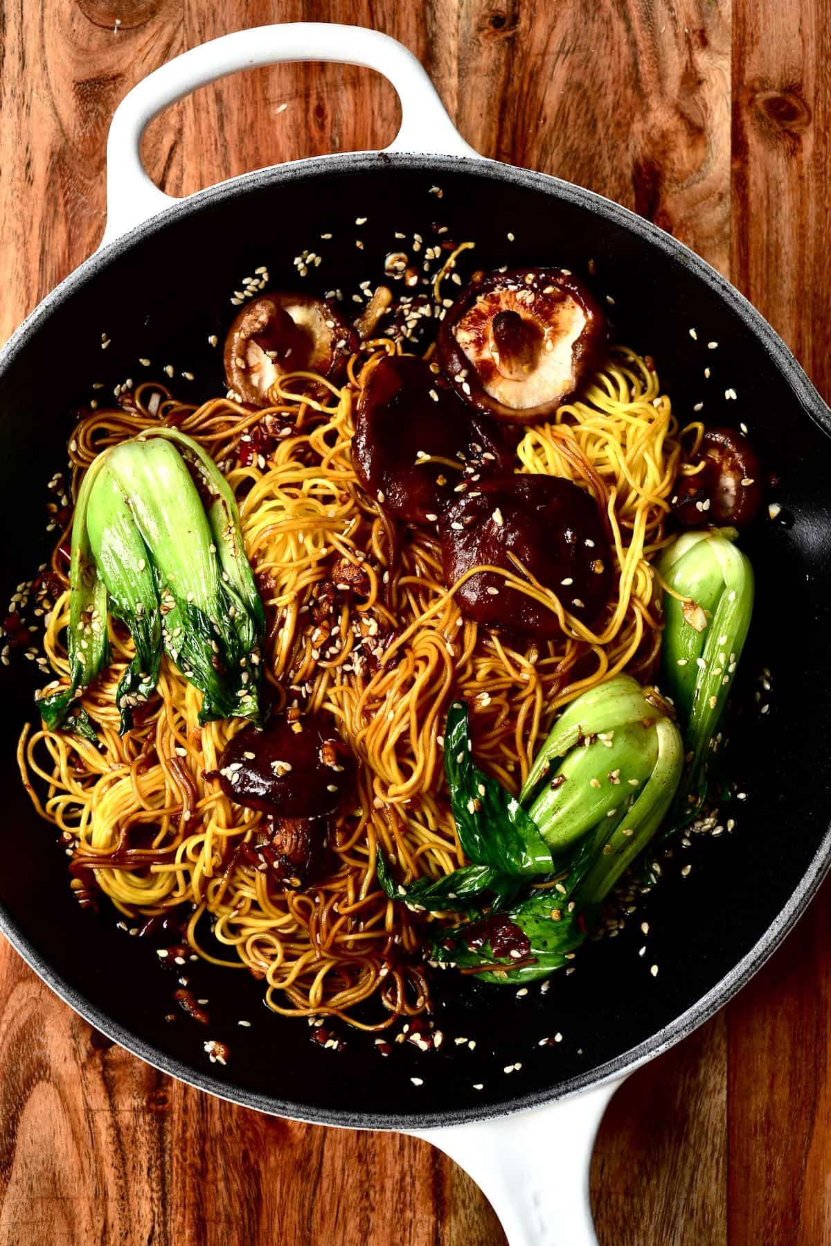 Dan dan noodles with bok choy and mushrooms in a pan