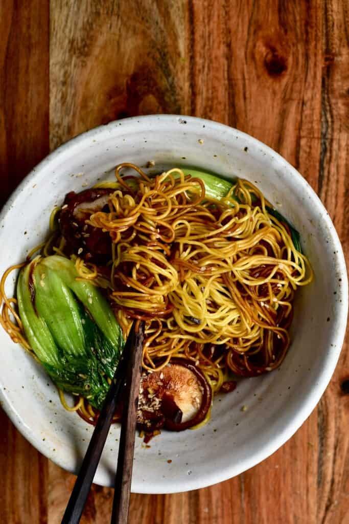 Dan dan noodles with bok choy and mushrooms in a bowl