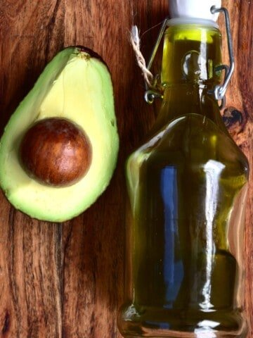 Half an avocado and a small bottle with homemade avocado oil