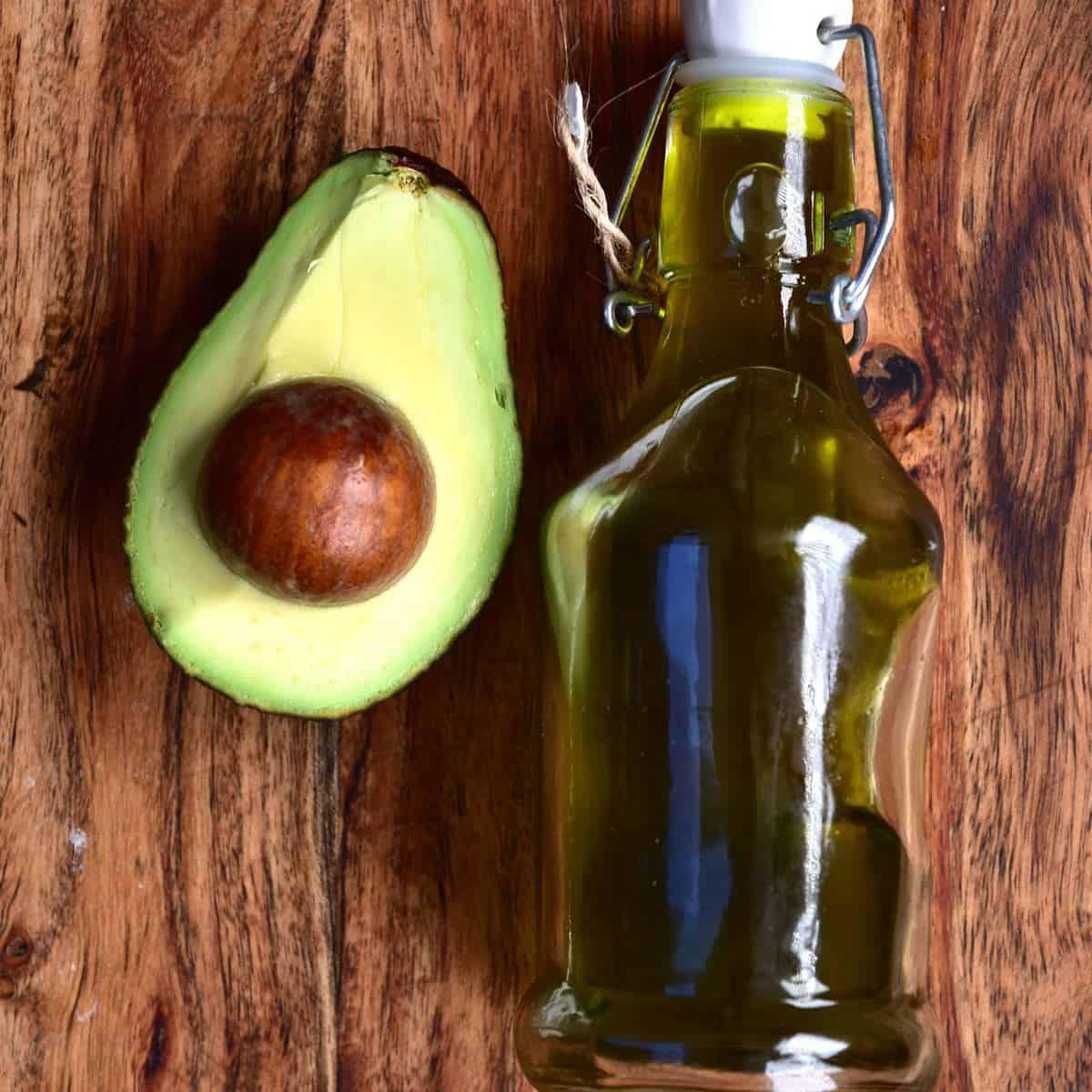 Half an avocado and a small bottle with homemade avocado oil