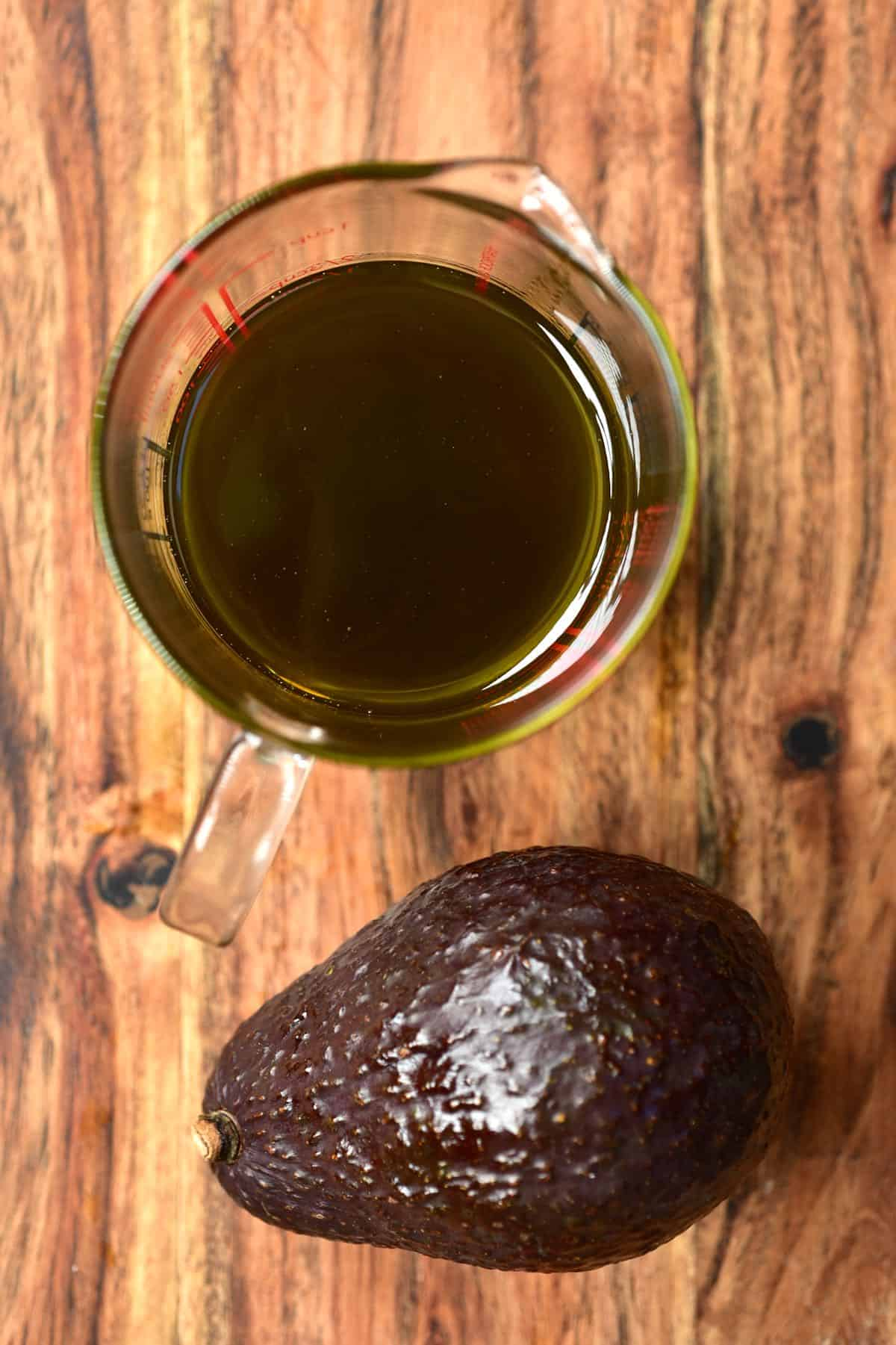 One avocado and a small jug with avocado oil