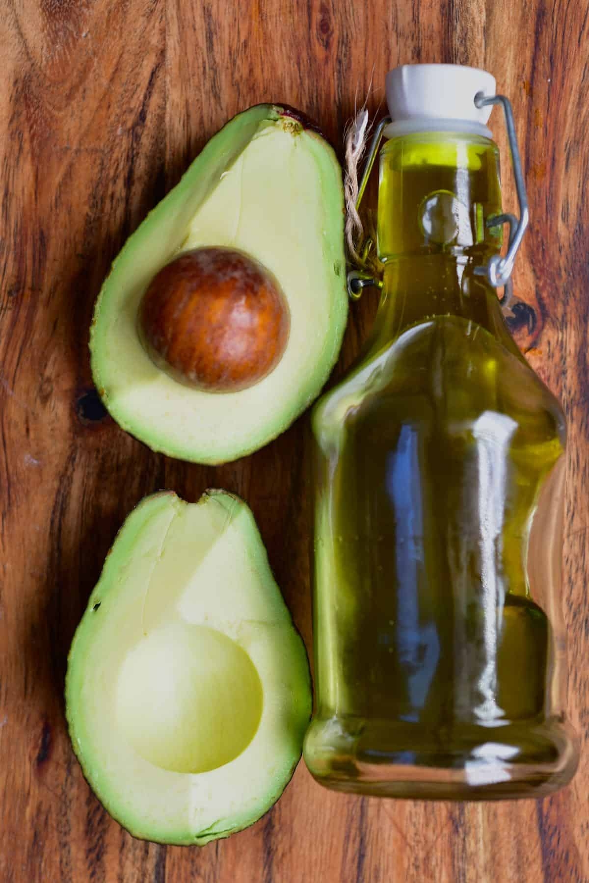 Avocado sliced in two and a small bottle with homemade avocado oil