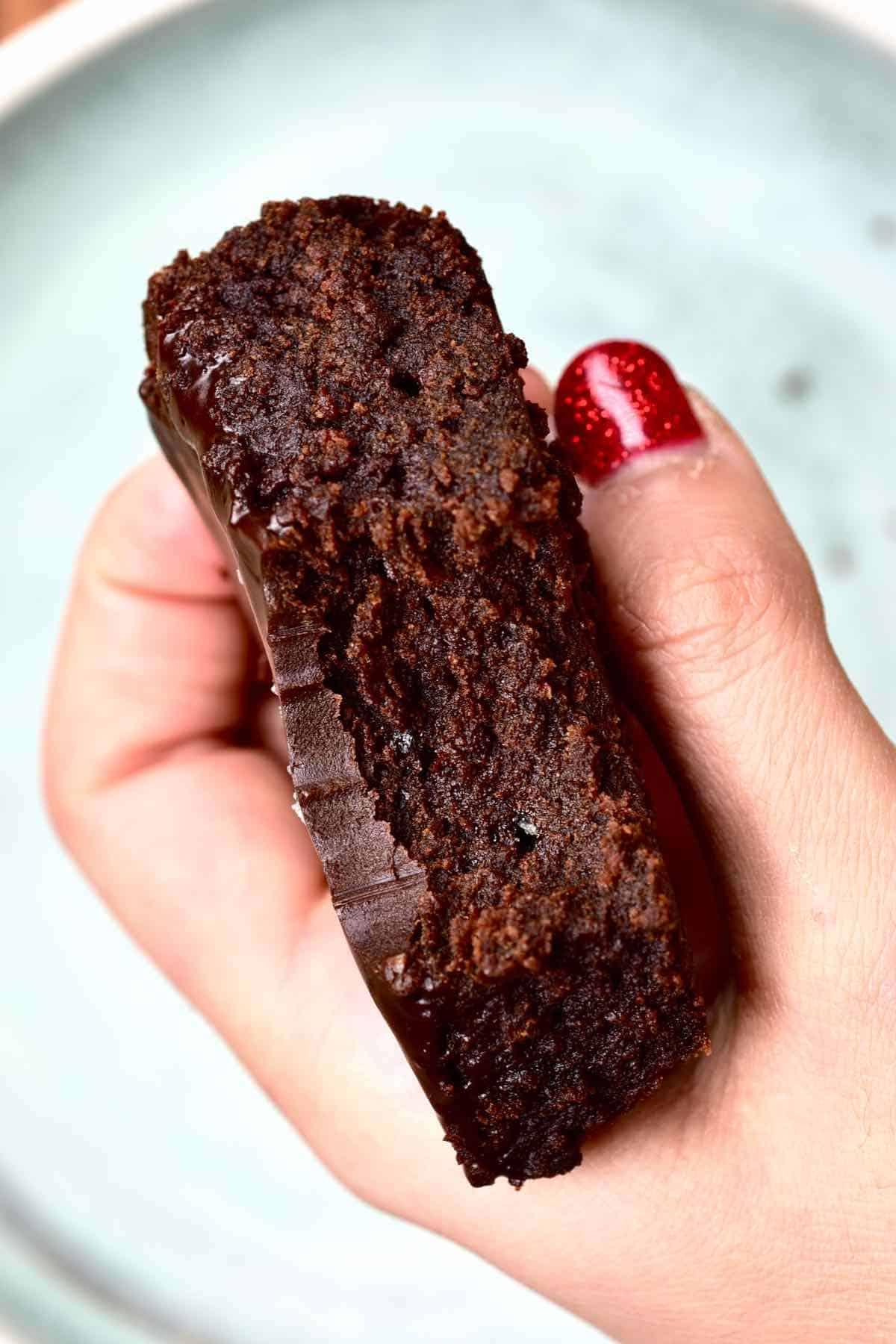 A hand holding a half eaten brownie piece