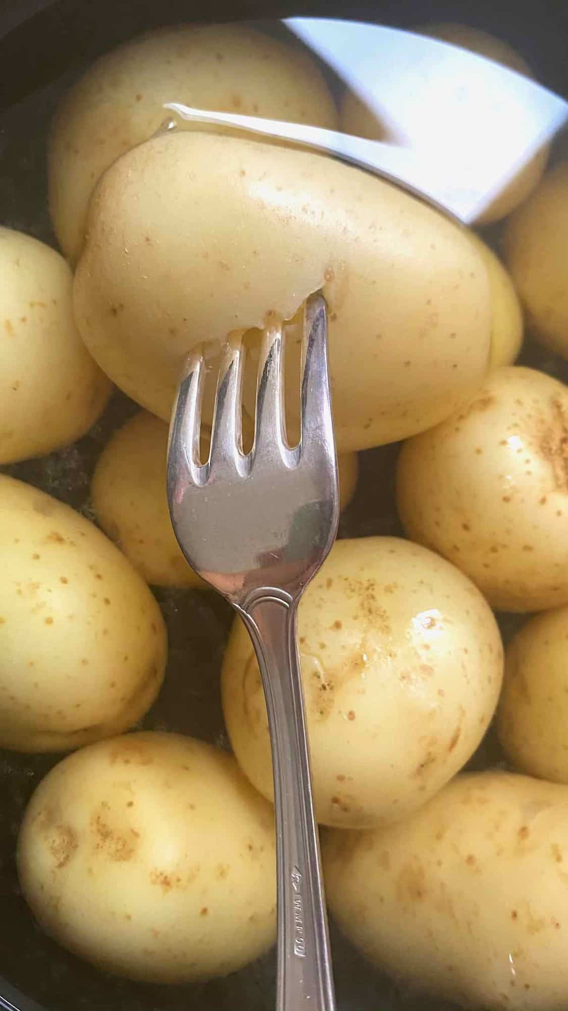 Fork poking a boiled potato in a pot