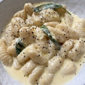Gnocchi in a bowl topped with black pepper and sage