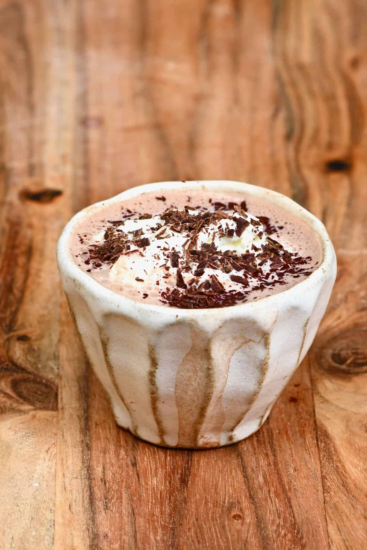 Hot chocolate in a small cup with chocolate shavings on top