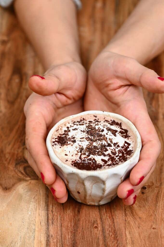 Hands holding a small cup with hot chocolate