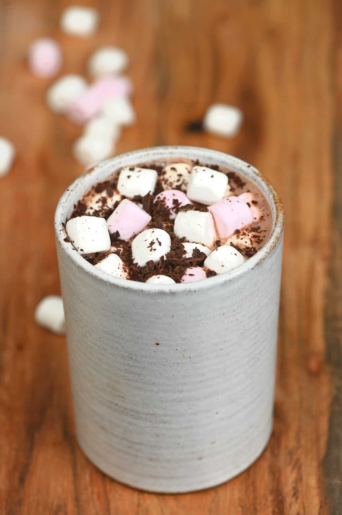 Hot chocolate in a cup topped with marshmallows and chocolate shavings