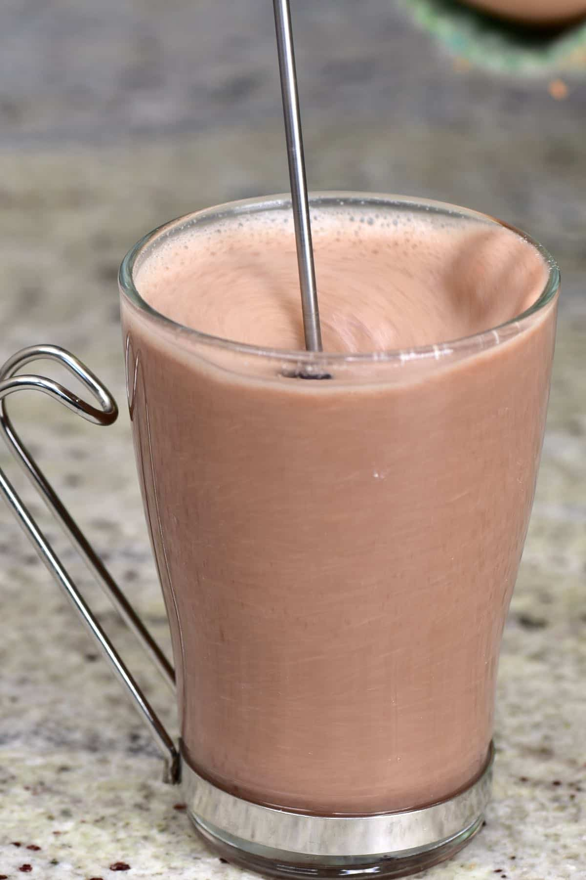 Stirring hot chocolate in a glass