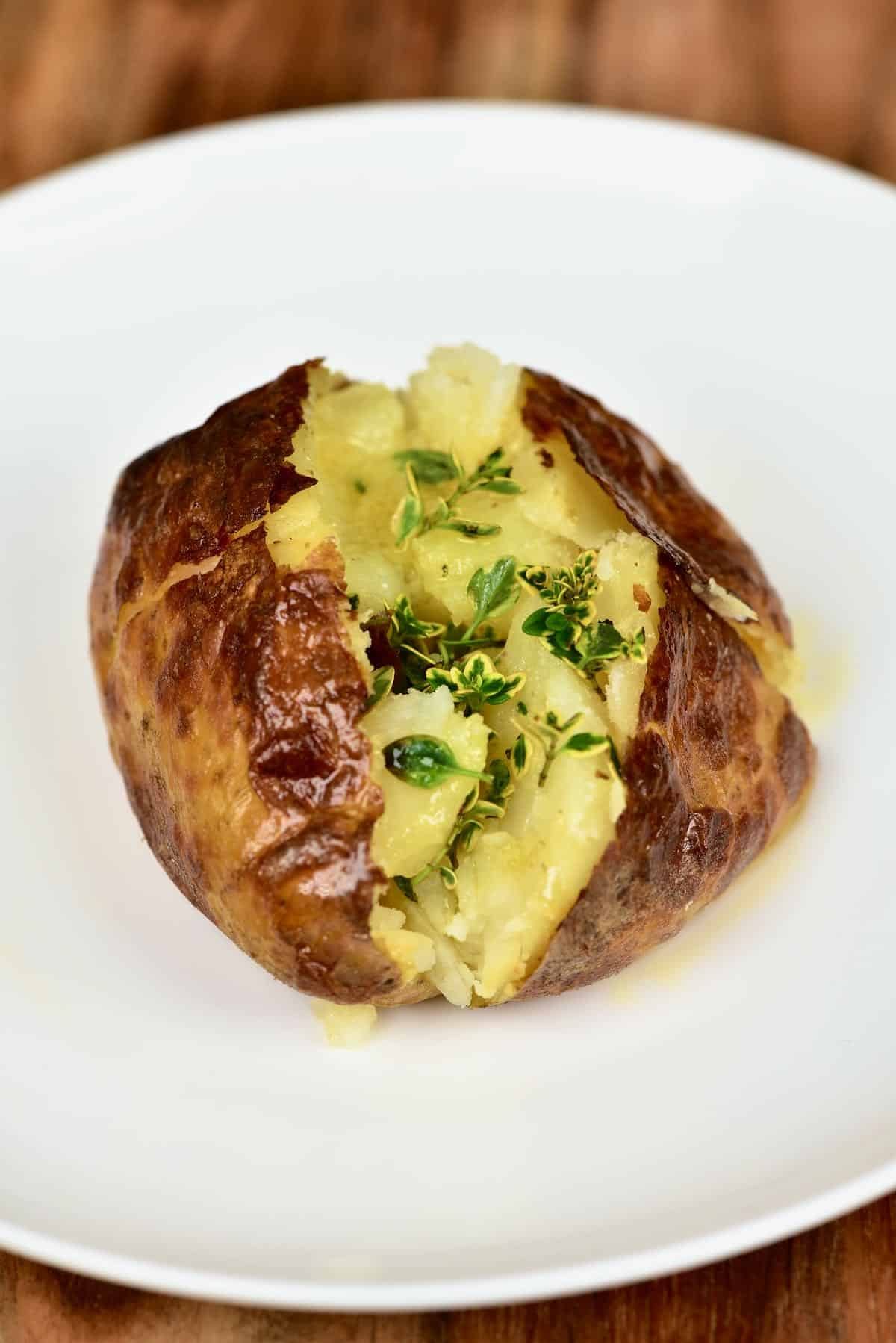Salt baked potato in a plate topped with thyme