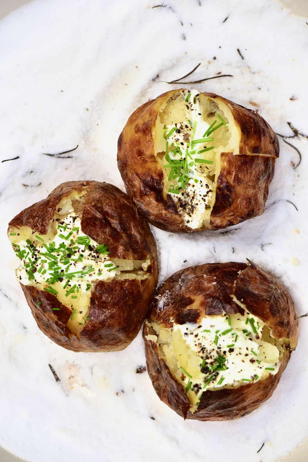 Three salt baked potatoes topped with cream and herbs