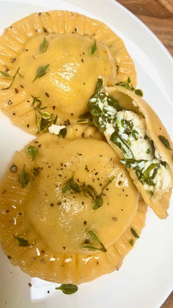 Three homemade ravioli with spinach filling in a plate