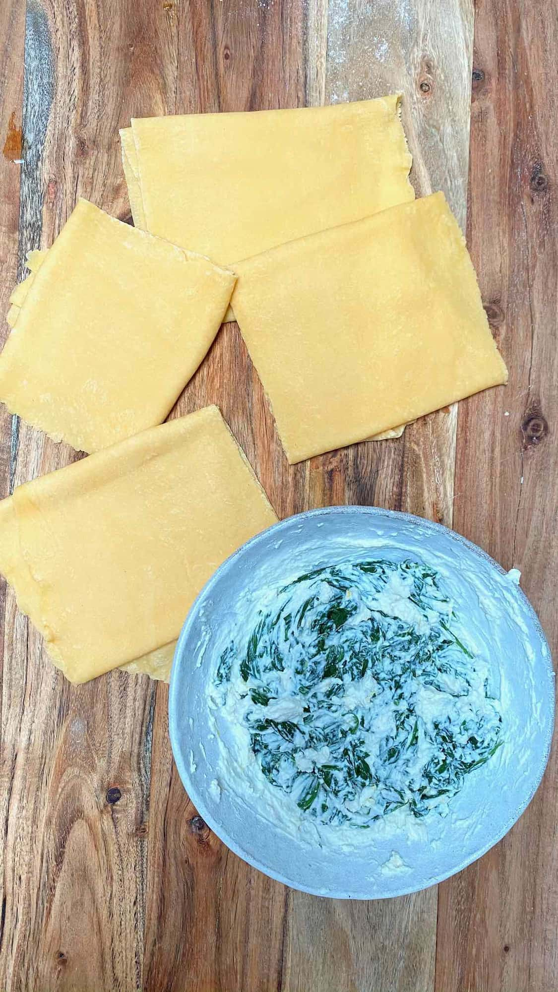 Four sheets of though and spinach ricotta filling in a bowl