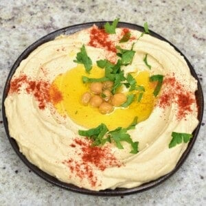 A bowl with hummus topped with some oil, chickpeas, paprika and coriander