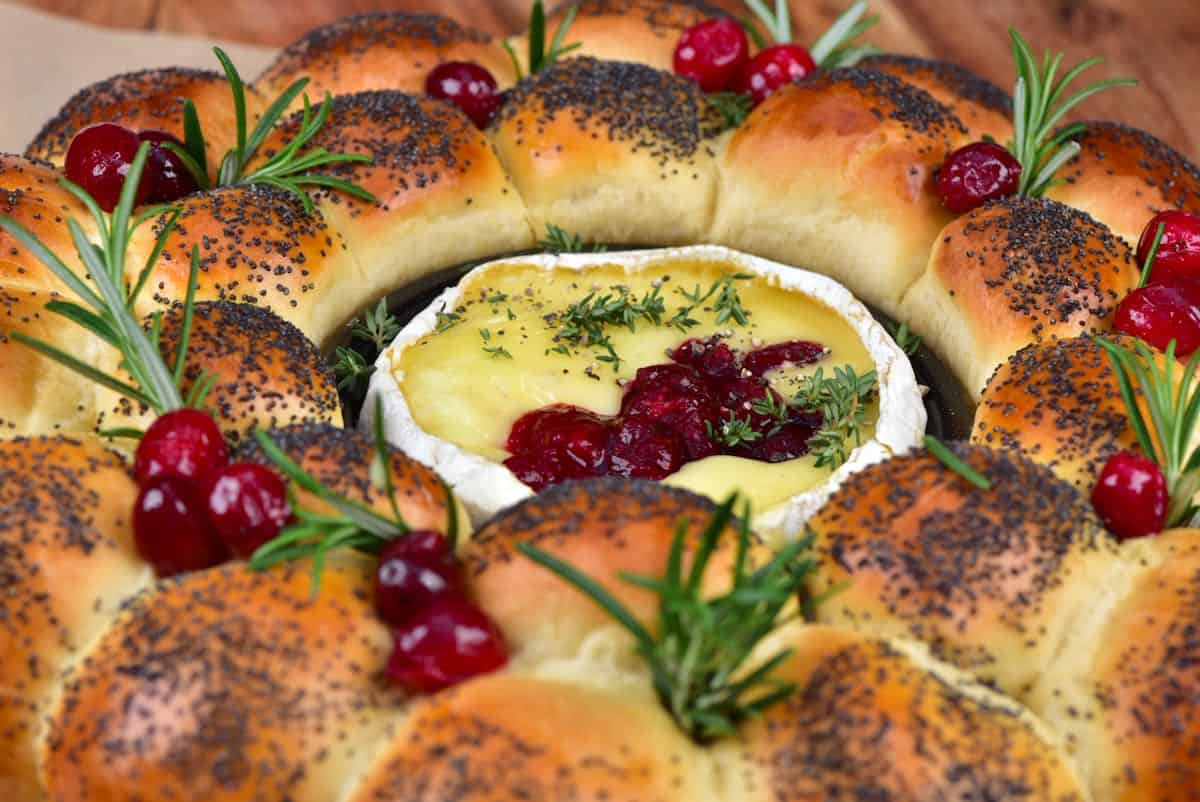 Dinner roll bread wreath with camembert center topped with cranberries and rosemary