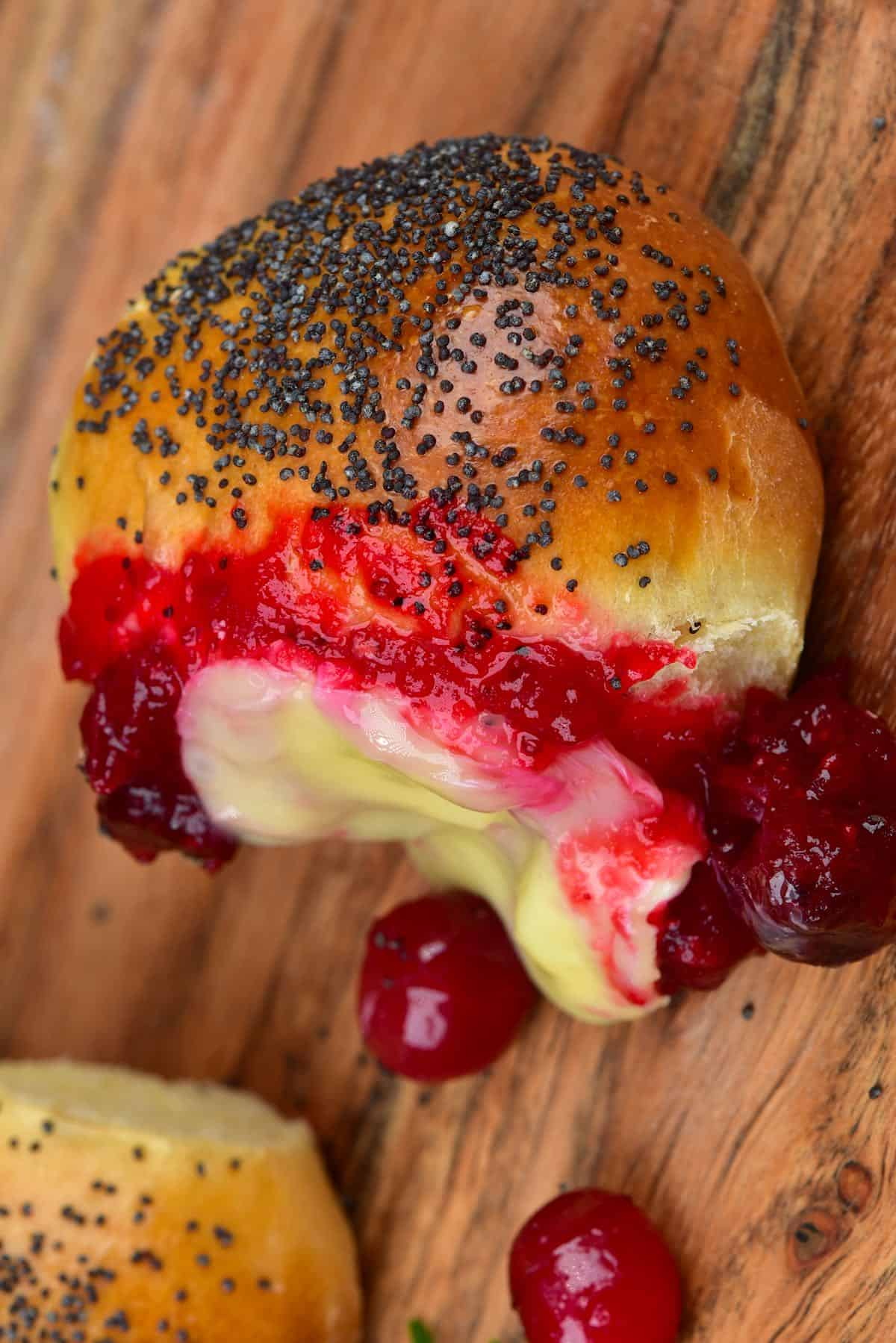 A bun with some melted camembert and cranberries