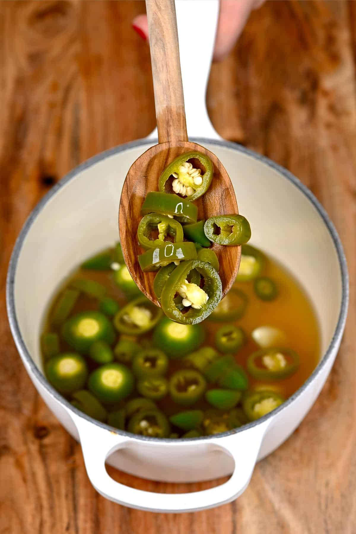 Pickled jalapeños in a wooden spoon