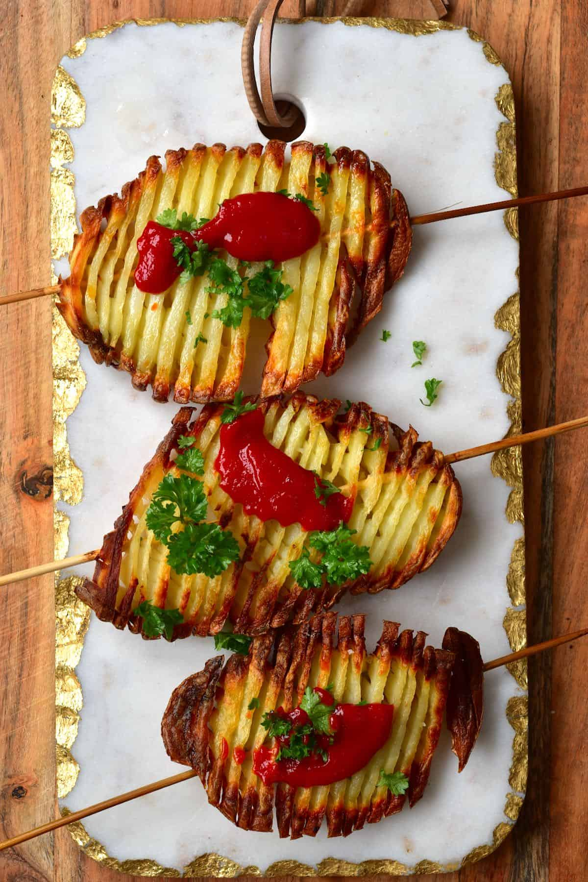 Three accordion potato chips on skewers topped with some parsley and ketchup