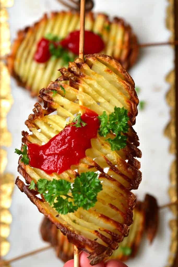 Accordion potato chip on a skewer topped with some parsley and ketchup