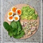 Breakfast tortilla with boiled egg, mashed avocado, spinach and pickles