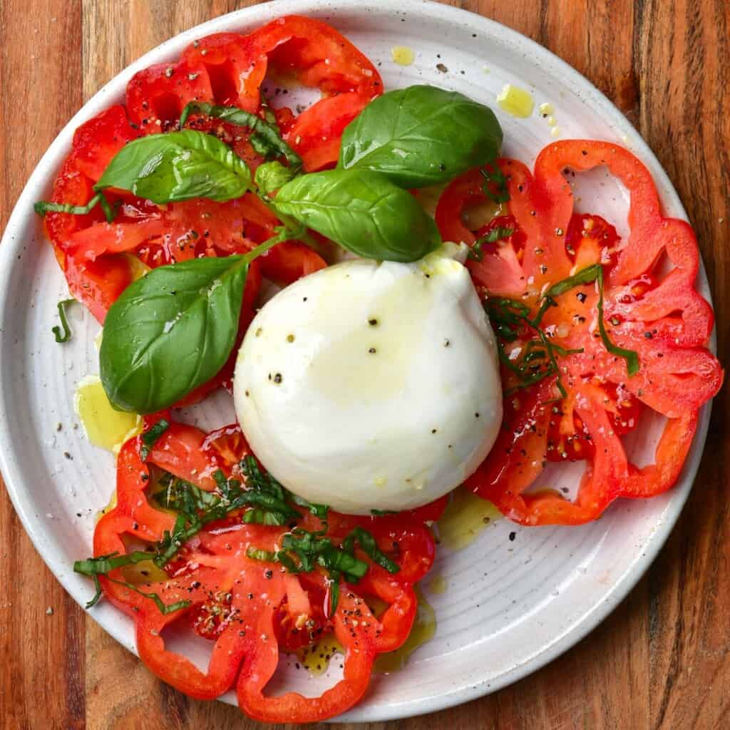 Sliced tomatoes and burrata cheese on a plate