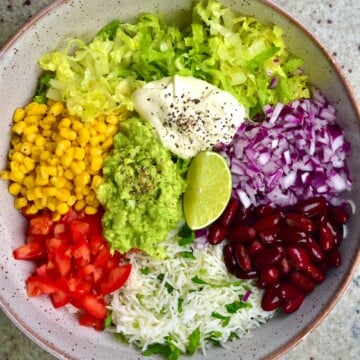 Rainbow veggies like lettuce, corn, beans, tomatoes and avocado in a bowl