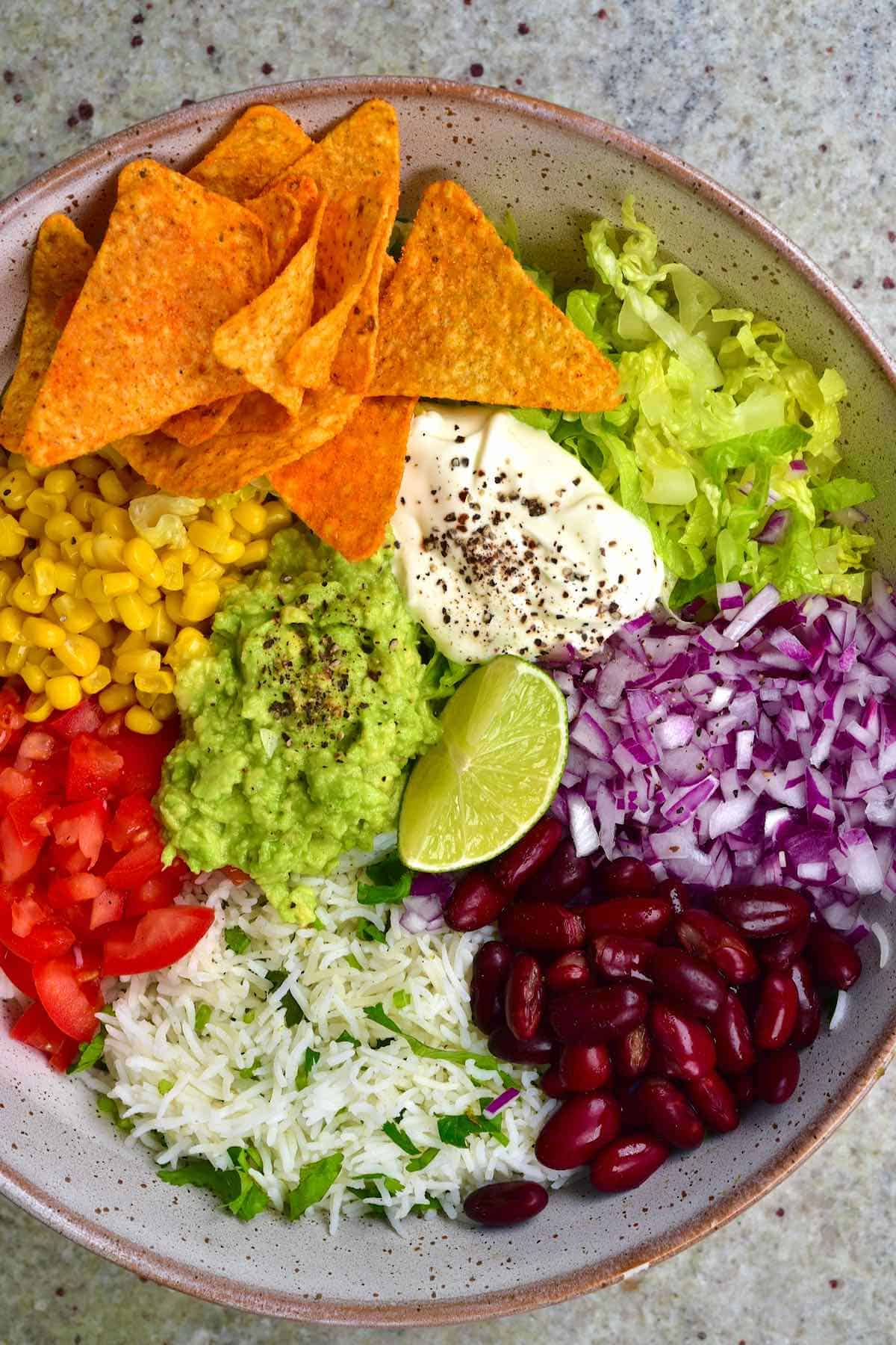 A bowl filled with rice, lettuce, corn, other veggies and corn chips