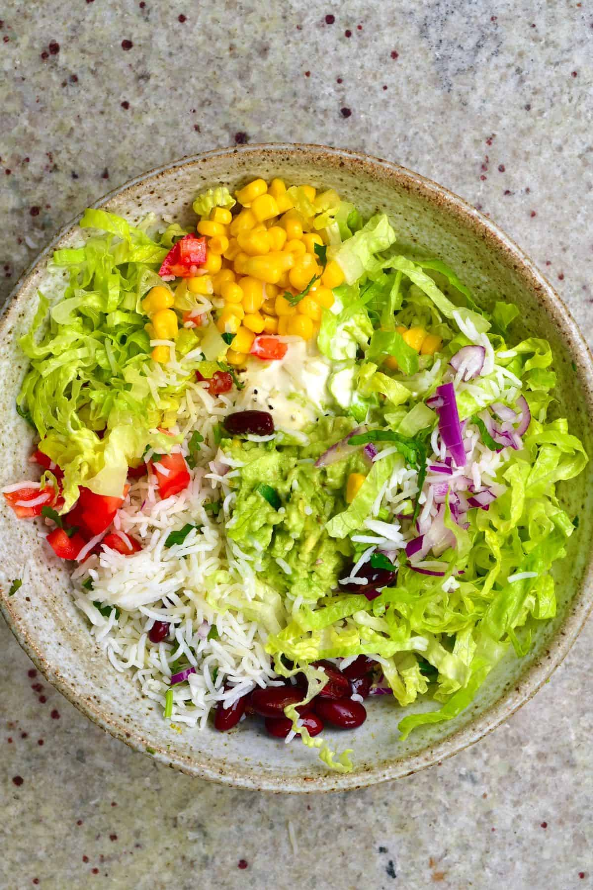 A veggie burrito bowl filled with rice, lettuce, corn and other veggies