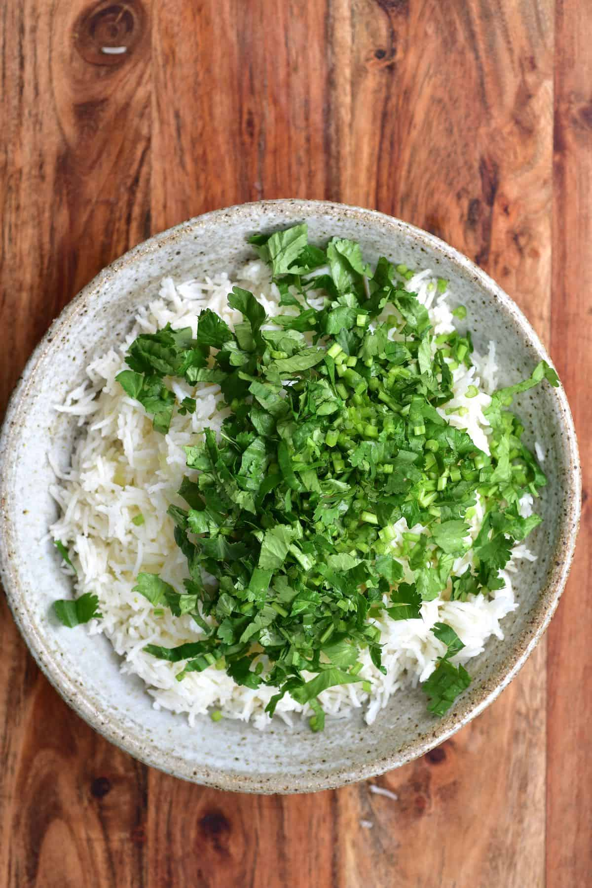 A bowl of basmati rice and chopped cilantro