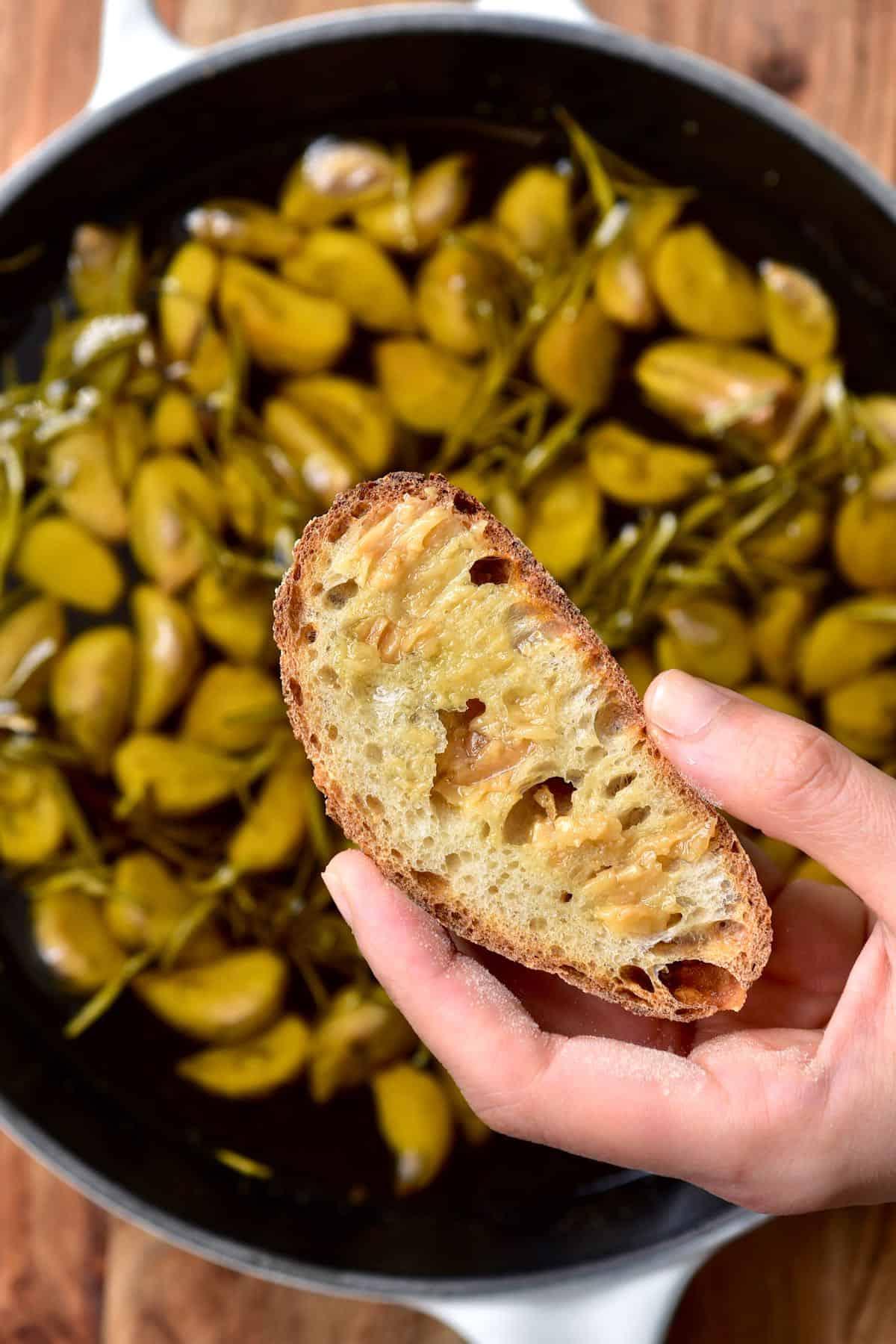 Garlic confit spread on a piece of bread