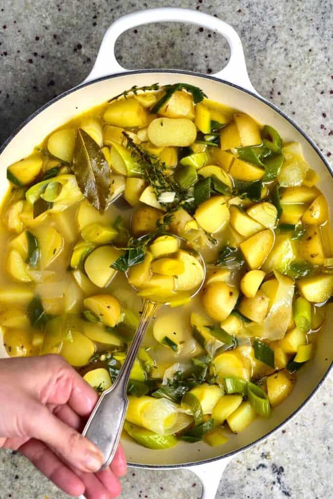 A pot with potato leek soup and a ladle