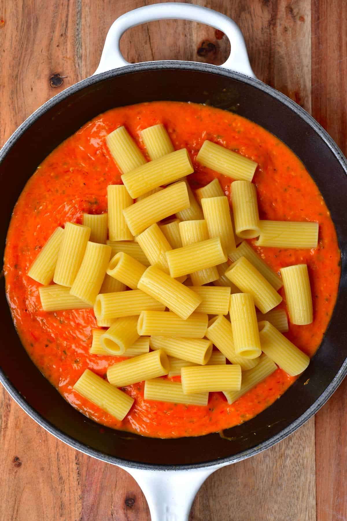 A pan with tomato sauce and some penne pasta