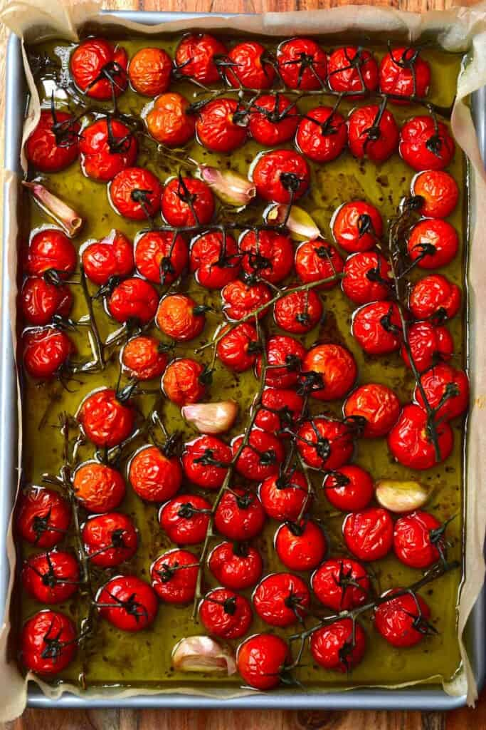 Tomato confit and garlic in a tray with oil