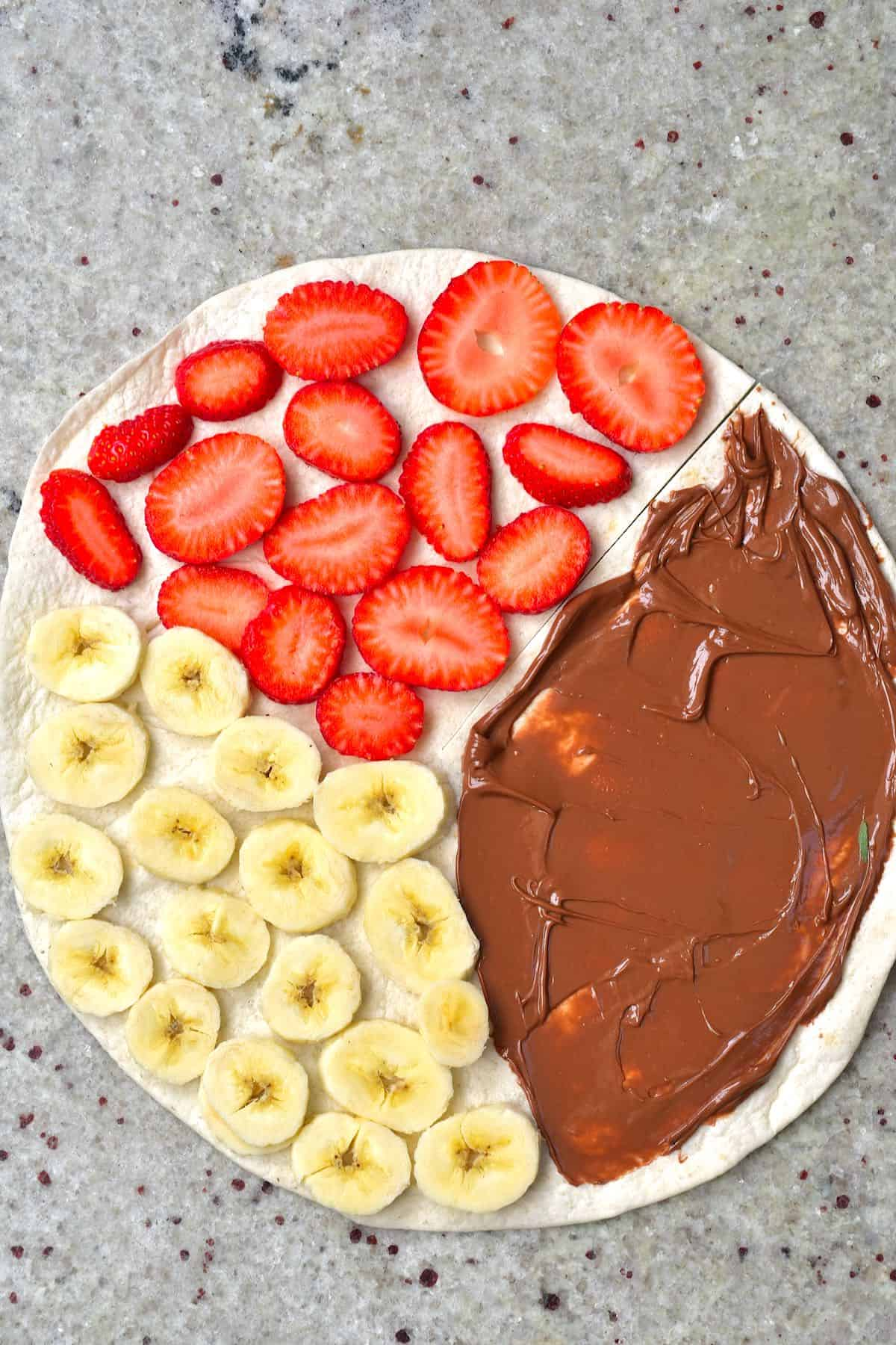 Tortilla topped with nutella banana slices and strawberry slices