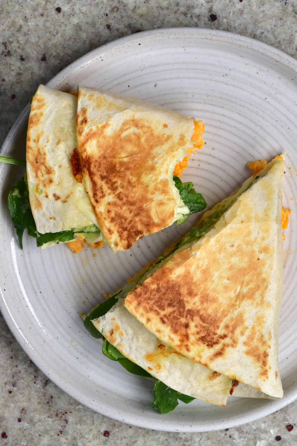 Tortilla wrap with spinach and scrambled eggs cut in two in a plate