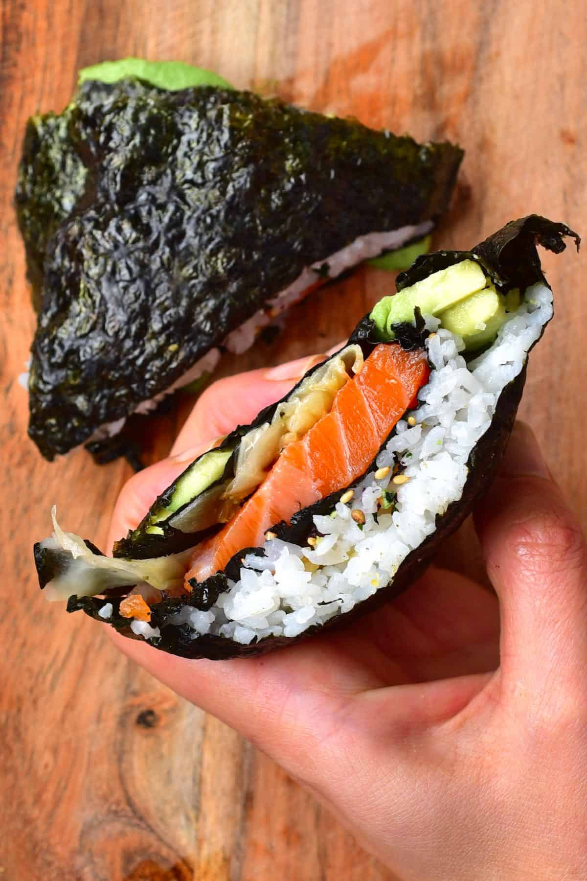 Sushi nori wrap with salmon cut in two, one half held in a hand
