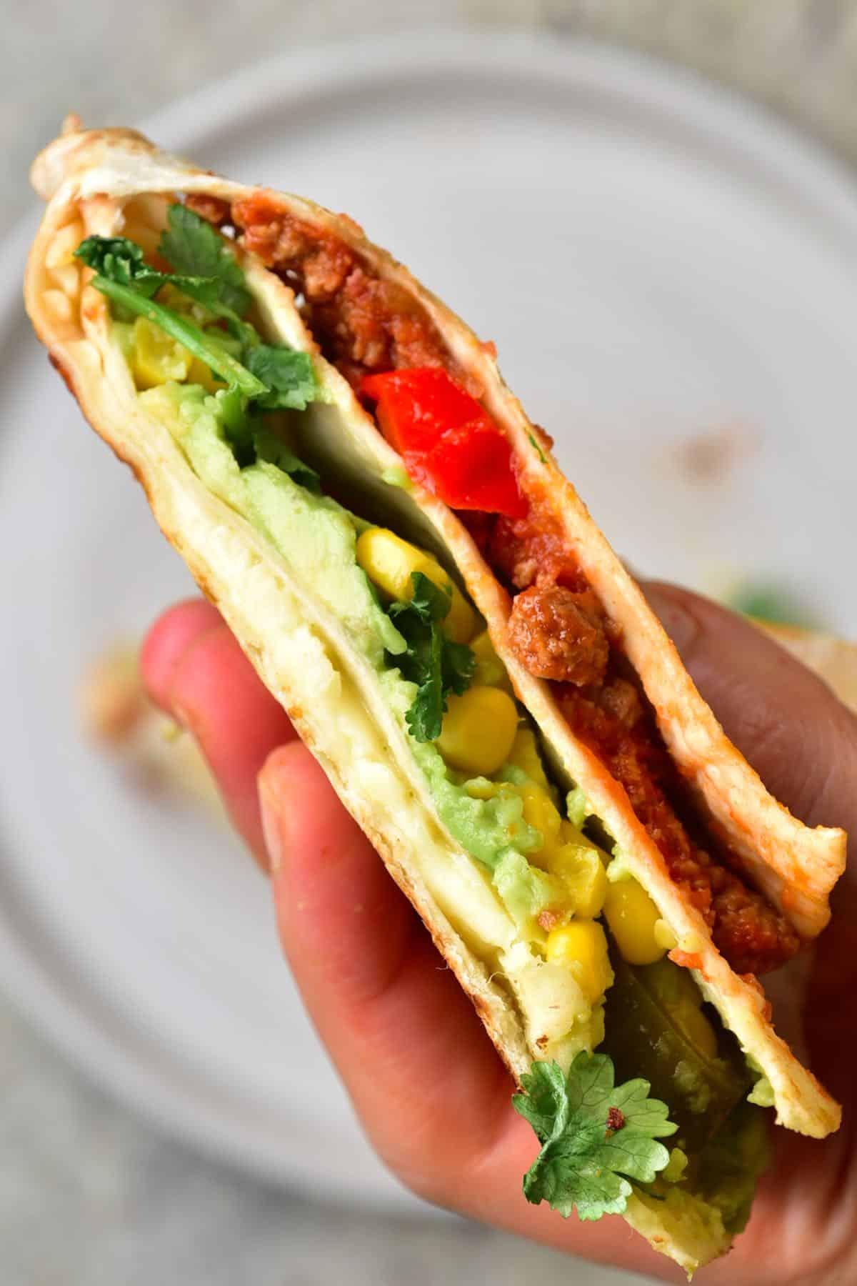 Tortilla wrap with vegan chili con carne, corn and avocado