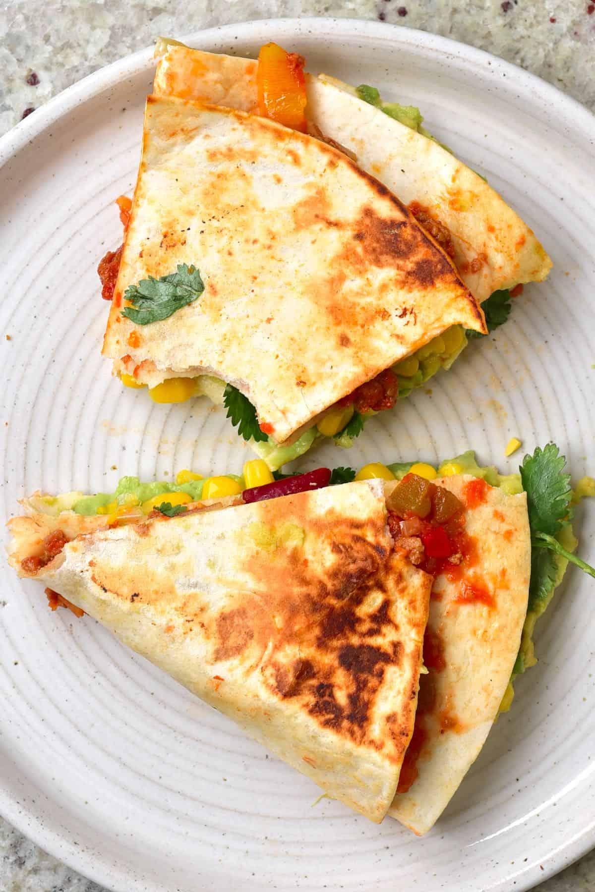 Tortilla wrap with vegan chili con carne, corn and avocado in a plate