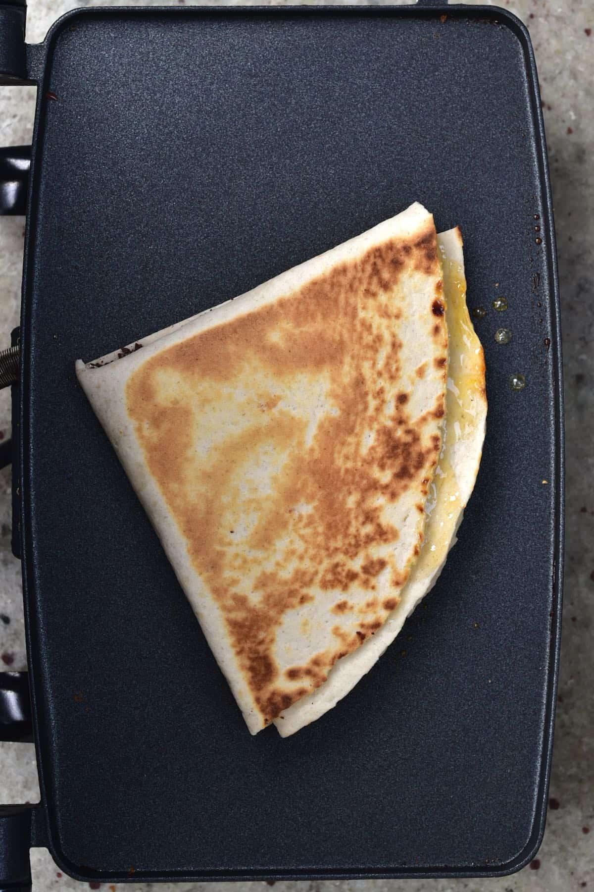 Tortilla being warmed up on a sandwich press