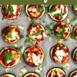 Twelve zucchini pizza bites arranged on parchment paper