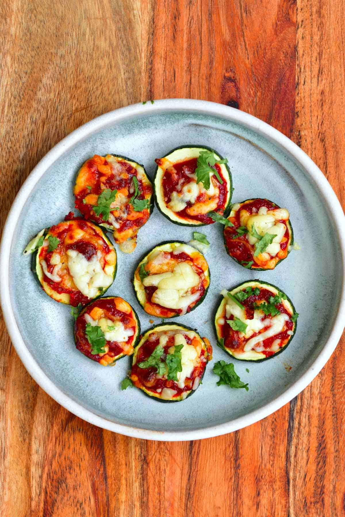 Eight zucchini pizza bites in a blue plate