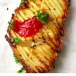 One accordion potato on stick topped with ketchup and parsley