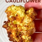 A close up of hand holding a roasted cauliflower floret