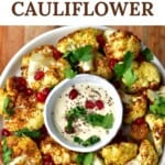 A plate with roasted cauliflower and a small bowl of white sauce