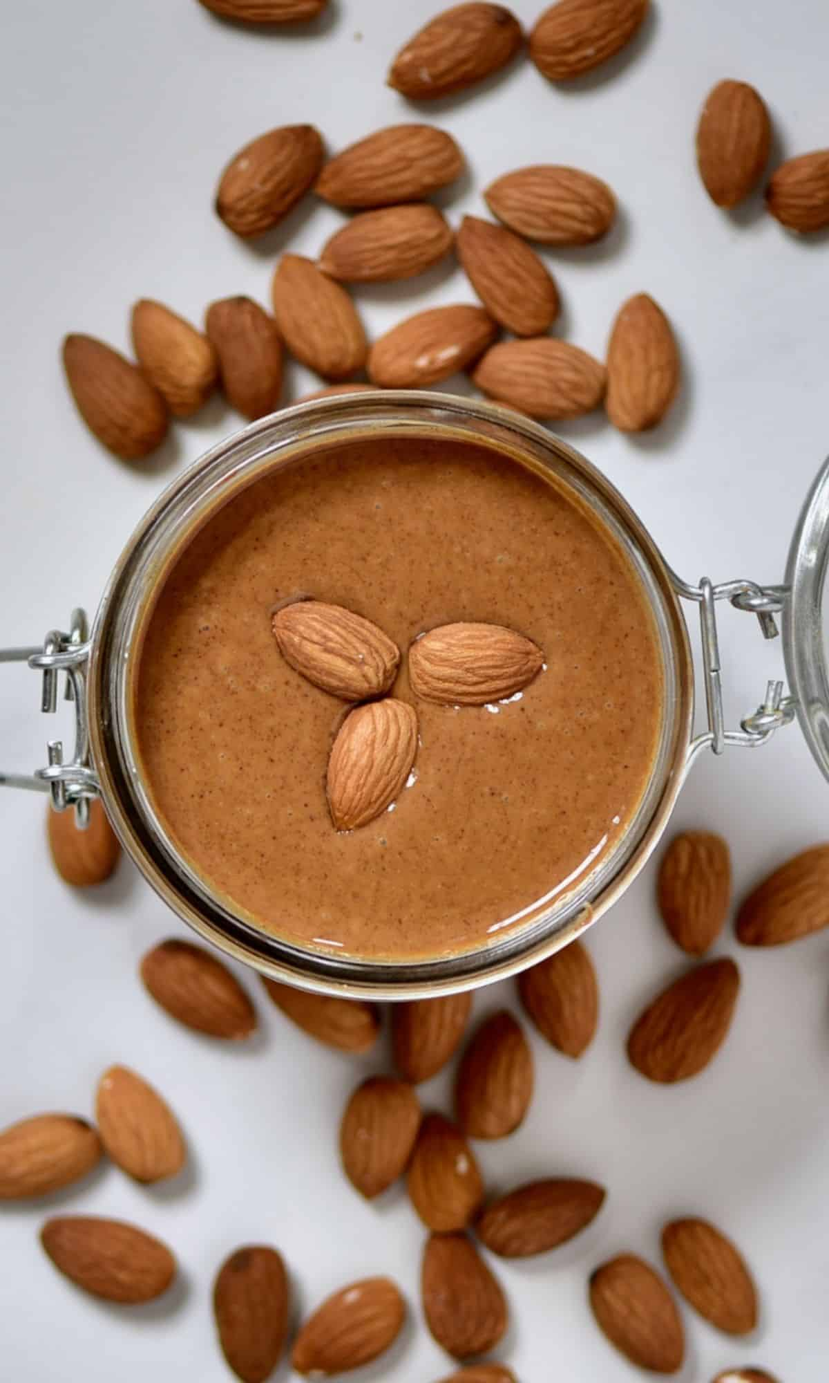 Almond Butter in a jar with almonds around it