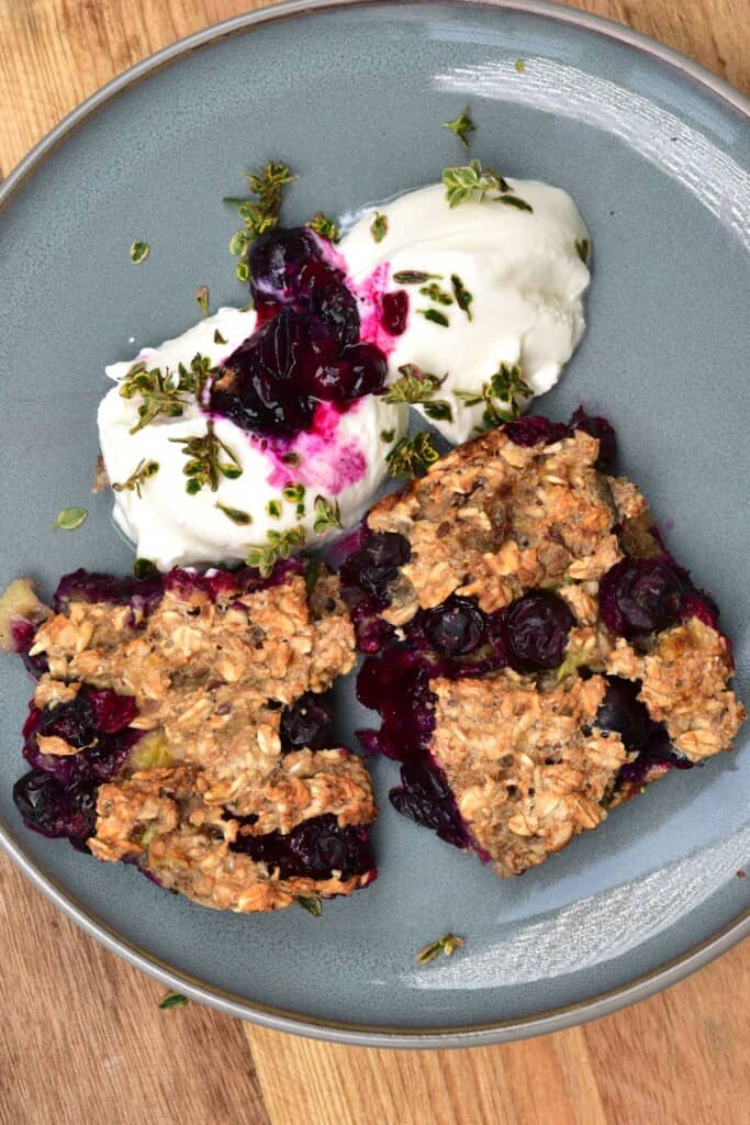 Two squares of baked blueberry oats served with yogurt