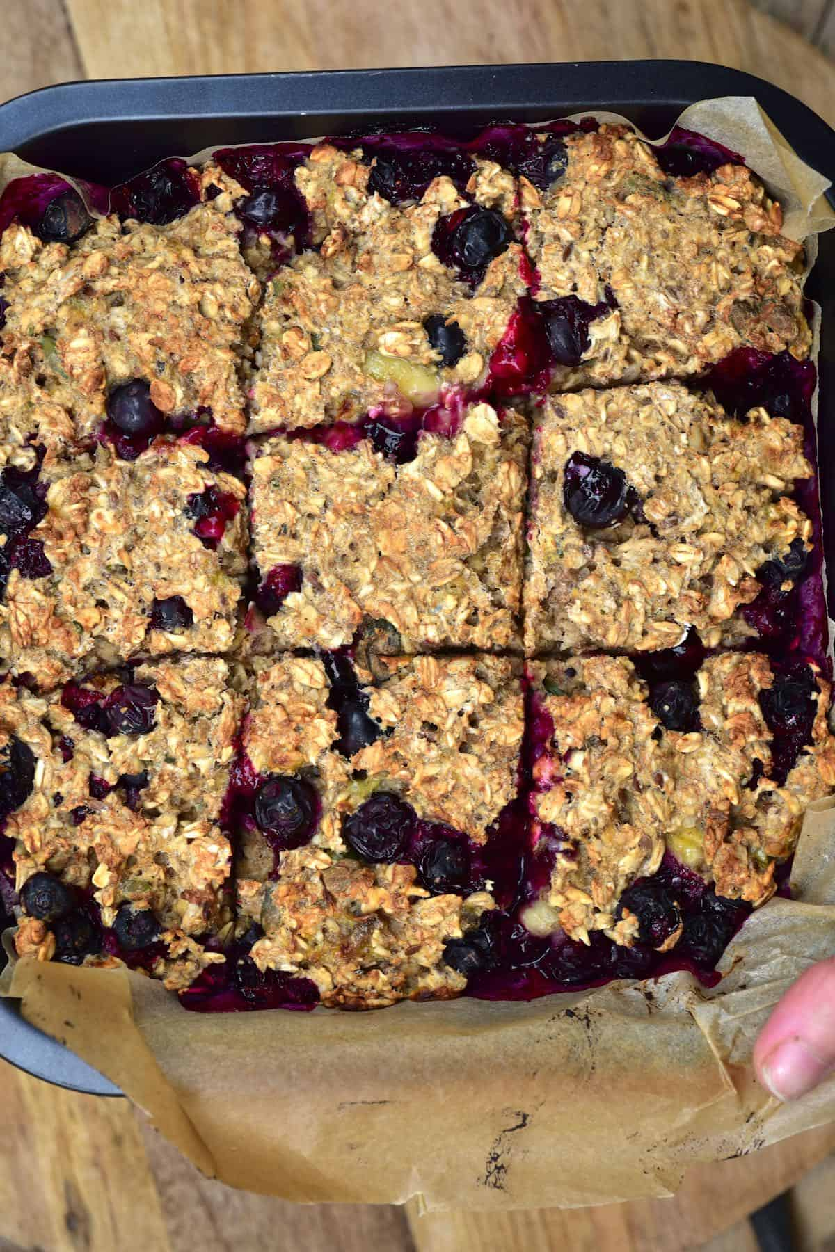 Baked blueberry oats in a baking tray cut into nine squares
