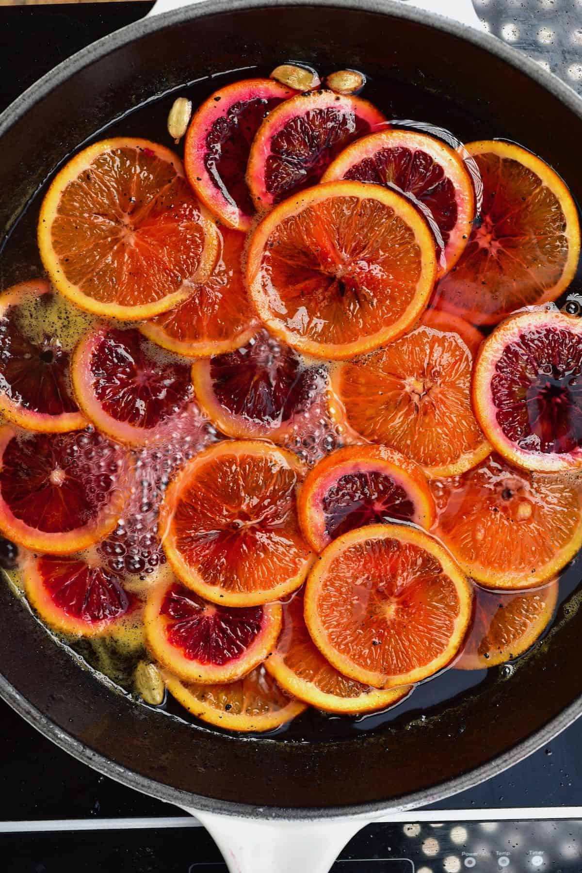 Orange slices in a pan with sugar syrup