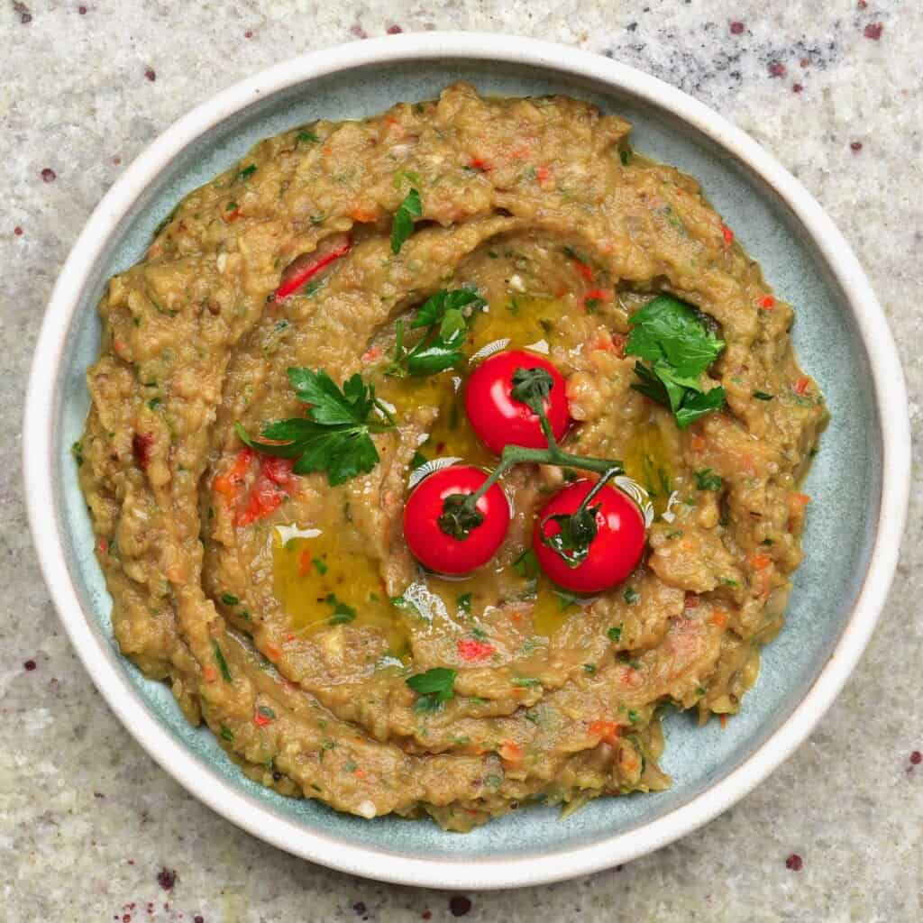 A bowl with Caribbean eggplant dip topped with three cherry tomatoes and cilantro