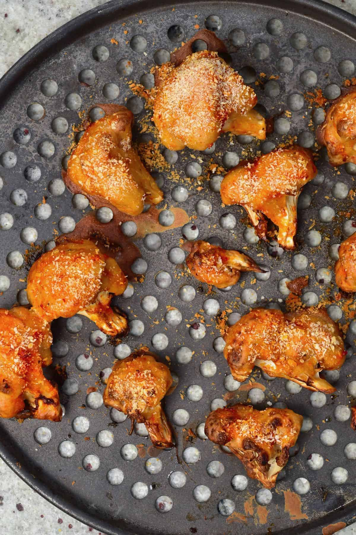 A baking tray with baked breaded cauliflower wings